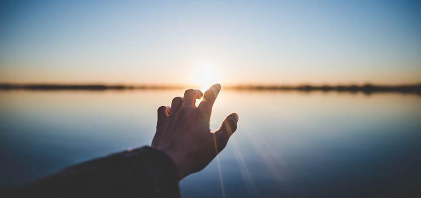 A hand reaching towards the sun.