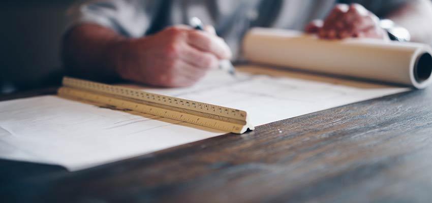 A man drafting a blueprint.